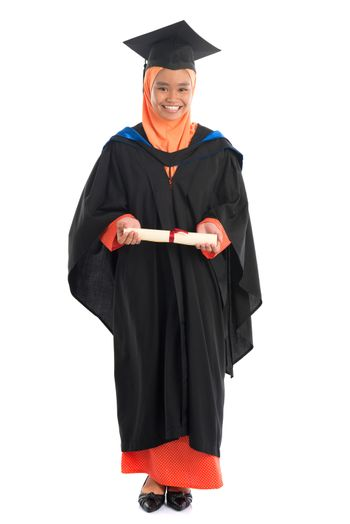 Full body female student in graduation gown, standing isolated white background.