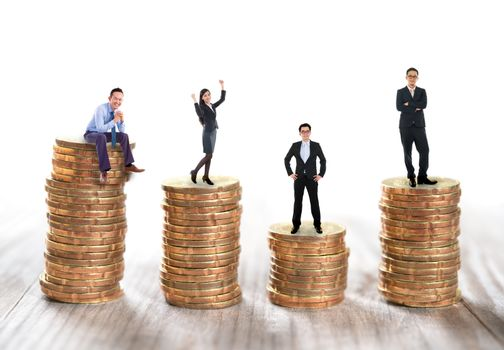 Miniature business people sitting and standing on stack of coins.