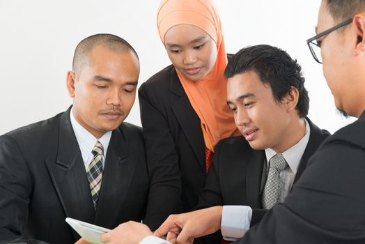 Group of Malaysian businesspeople meeting or having discussion on desk inside office room.