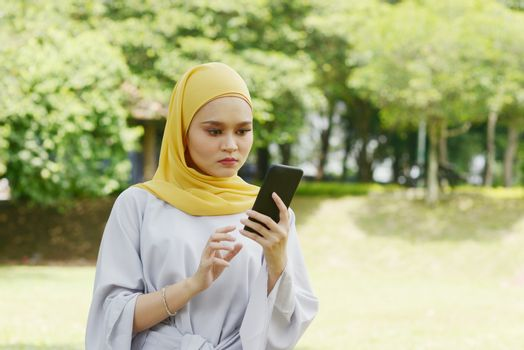 Muslim woman looking at mobile phone, negative emotions, phishing scams concept.
