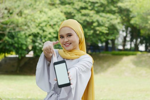 Portrait of cheerful Muslim girl hand pointing at smartphone, smiling at outdoor.