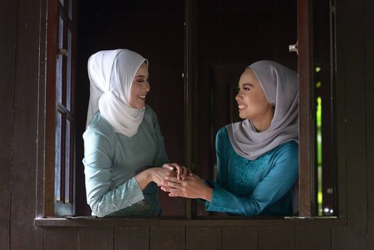 Asian Malay Muslim girls greetings during Hari Raya Aidilfitri. Malaysian people living lifestyle.