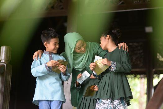 Muslim family, children received money packet as blessing, Hari Raya Eid Al-Fitr concept.