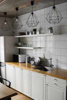 Modern, bright, clean, kitchen interior with stainless steel appliances in a luxury house. Kitchen in luxury mansion. Modern architecture contemporary, interior. Stylish kitchens interior with table.