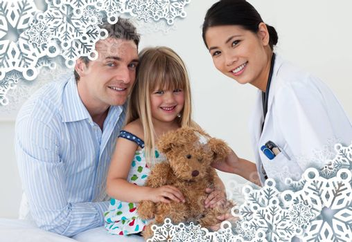 Portrait of a doctor and happy little girl examing a teddy bear against snowflake frame