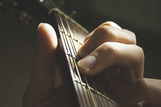 Man's hands fingers on the acoustic guitar strings close up macro shot on sun shine. Music, hobby and leisure