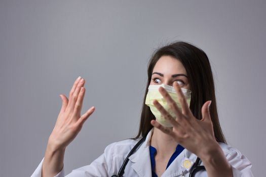 Nurse practitioner or Physician's assistant holding hands up in shock while wearing a mask. Possible contamination from coronavirus