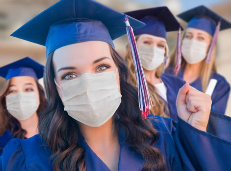 Several Female Graduates in Cap and Gown Wearing Medical Face Masks.