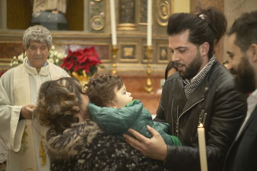Father with son at baptism in a catholic celebration in Italy