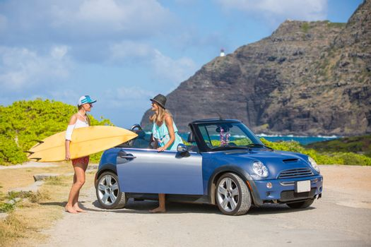 Friends laughing having fun in Oahu island, USA travel lifestyle. Hawaii surfers people lifestyle happy living friends talking on beach relaxing from surfing with surfboard