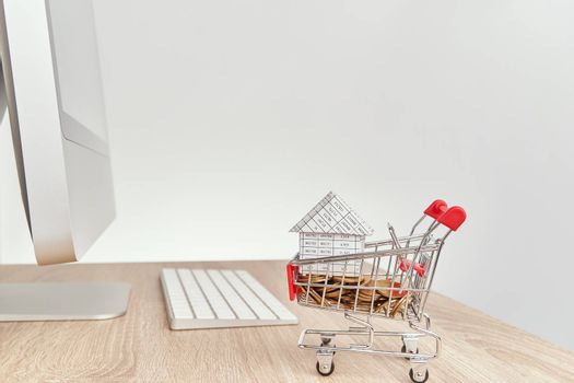 House gold coins in shopping cart on wooden computer table
