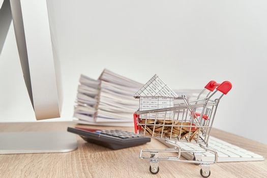 House gold coins in shopping cart on computer table