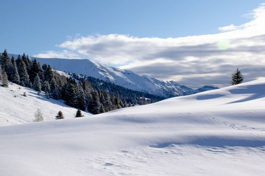 beautiful image of the snow-capped Mount Portule with clouds and woods near Cima Larici in Asiago