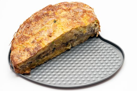Homemade yeast-free cake on kefir with a filling of canned fish and potatoes, close-up. A hearty dish for a Flexitarian