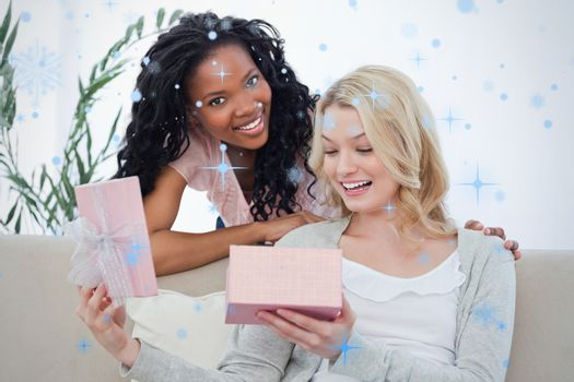 Woman opens a box containing a present and her friend smiles
