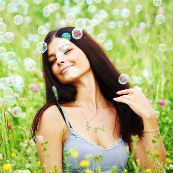 Happy woman smile in green grass soap bubbles around