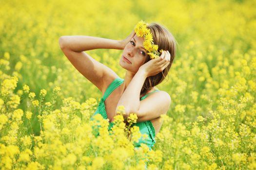 Pretty happy woman in dandelions wreath enjoy nature, happy cheerful girl resting on oilseed field