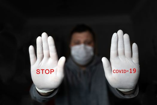 A man in a medical mask and gloves shows STOP with two hands, with the red text STOP COVID 19. on a dark background. Coronavirus infection protection concept