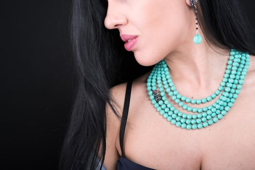 Young woman with beautiful jewelry on black background, closeup