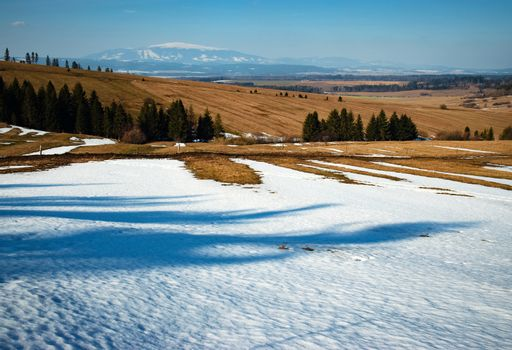 season nature background spring snowy landscape with a meadow