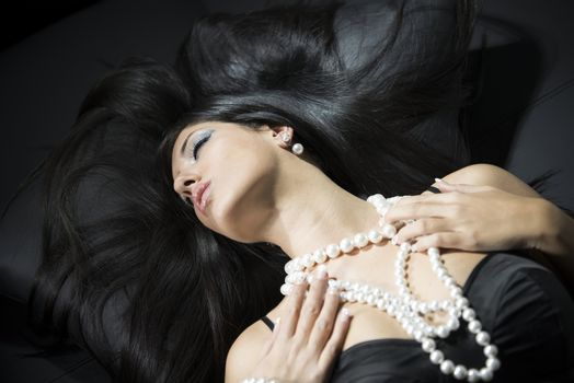 Beautiful woman with a pearl necklace and earring on the sofa. S