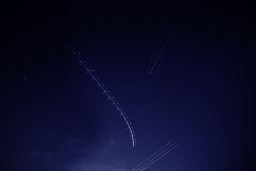 Multiple flying Airplane light trails blinking in the dark sky long exposure photography