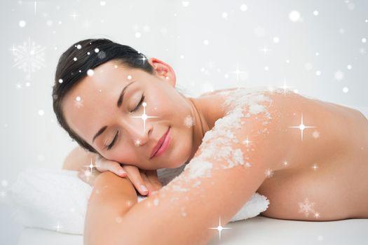 Peaceful brunette lying with salt scrub on shoulders