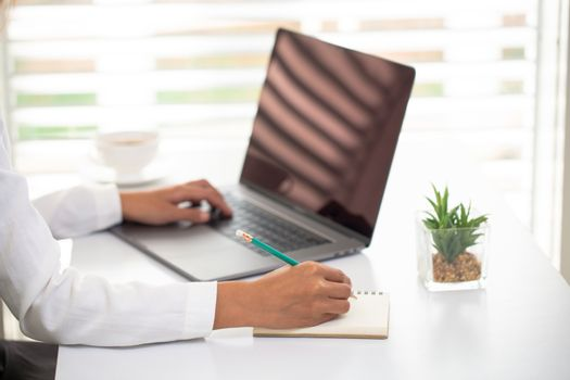 Business people work Laptop screen The hand is taking notes Office room. Online marketing concepts, adult education, e-learning Office work process Online training. Marketing accounting.