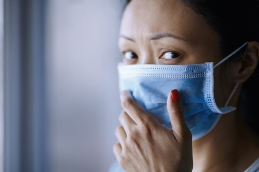 Woman staying at home wearing protective surgical mask