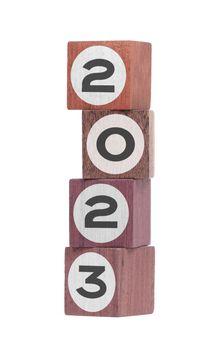 Four isolated hardwood toy blocks, saying 2023