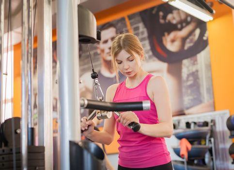 Woman doing fitness training on hand extension push machine