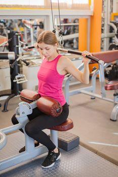Woman doing fitness training on leg extension push machine