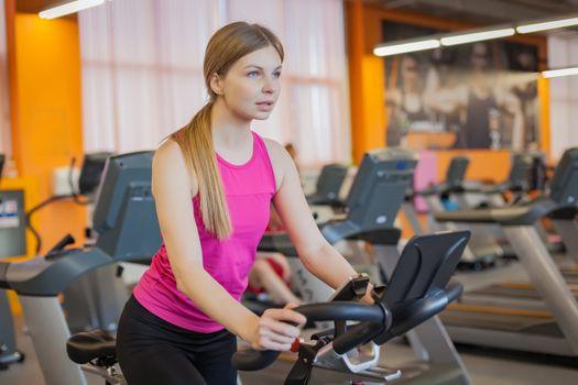 Woman doing cardio workout biking training in gym