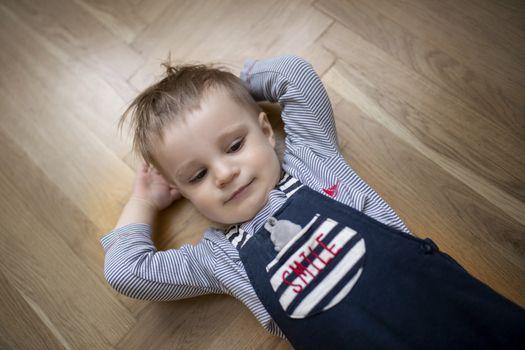 Boy lying on floor with hands behind his head