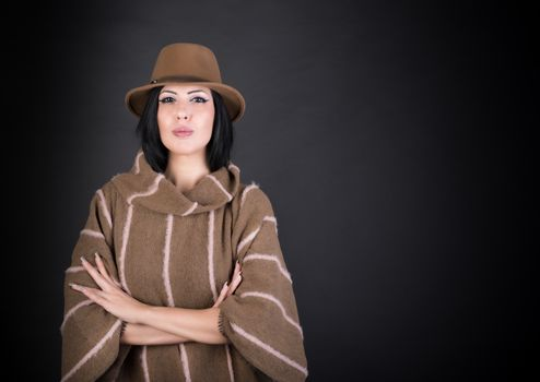 Fashion beautiful woman in country outfit and hat looking in cam