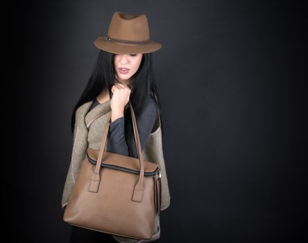 Fashion beautiful woman in country outfit, hat and bag