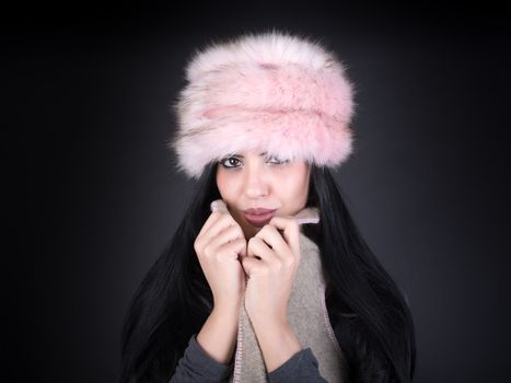 Winter portrait of a young woman in a pink hat on black backgrou