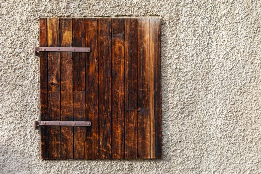 Classic aged wooden window made from hardwoods locked on outside of building with space of rough cement wall.