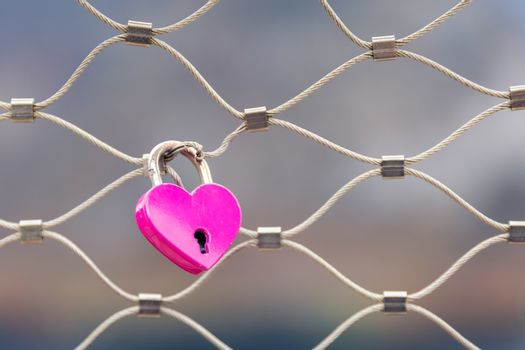 Close focus on pink lock in heart shape hanging on metal net fence with blurry background for loving representation.