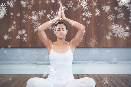 Peaceful woman in white sitting in lotus pose against snowflakes