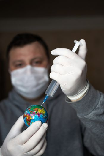 Man in medical mask and gloves making injection of coronavirus vaccine to planet earth. COVID-19 concept, global epidemic, cure for pandemic, stopping the epidemic, virus vaccine