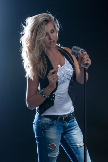 young, girl, blonde, jeans, clothes on a dark background emotion