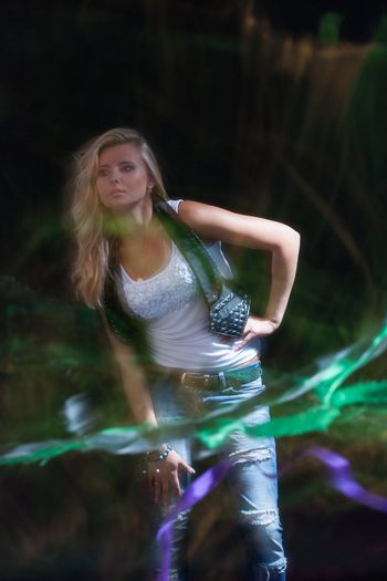 young, blonde girl in jeans clothes on a dark background