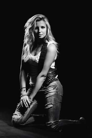 young, girl, blonde, jeans, clothes on a dark background kneels