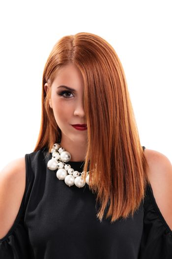Head shot of a beautiful redheaded young woman with clean make up, stylish black blouse and modern necklace, hair covering half of her face, isolated on white background. Fashion and beauty concept.