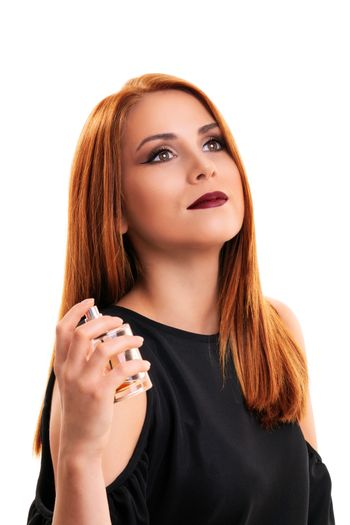 Close up of a beautiful young redheaded woman with elegant make up applying perfume on herself, isolated on white background. Elegant woman enjoying the scent of her perfume.