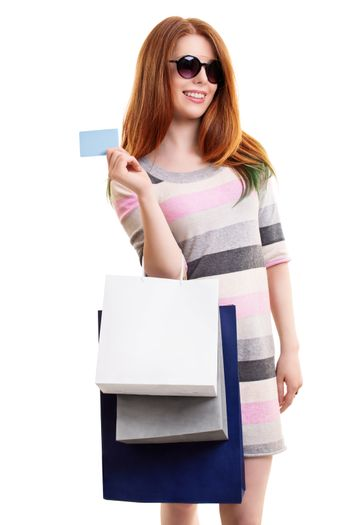 Portrait of a beautiful young girl in a dress with sunglasses, holing shopping bags and a blank card, isolated on white background. Shopping concept, copy space.