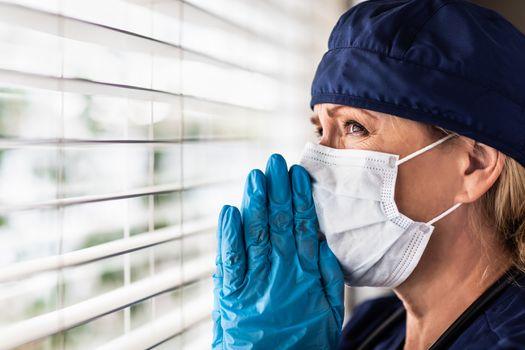 Prayerful Stressed Female Doctor or Nurse On Break At Window Wearing Medical Face Mask.