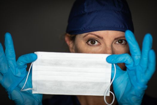 Female Doctor or Nurse Wearing Surgical Gloves Holding Up Medical Face Mask.
