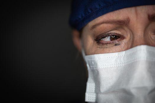Tearful Stressed Female Doctor or Nurse Wearing Medical Face Mask on Dark Background.